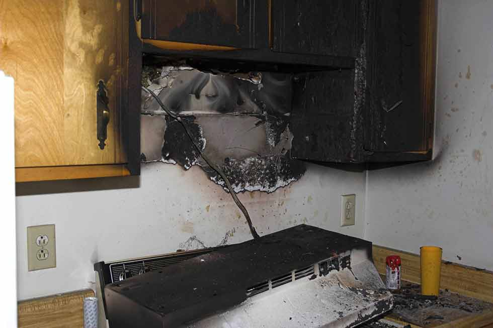 Fire Damage in a kitchen above a stove with burnt cabinets