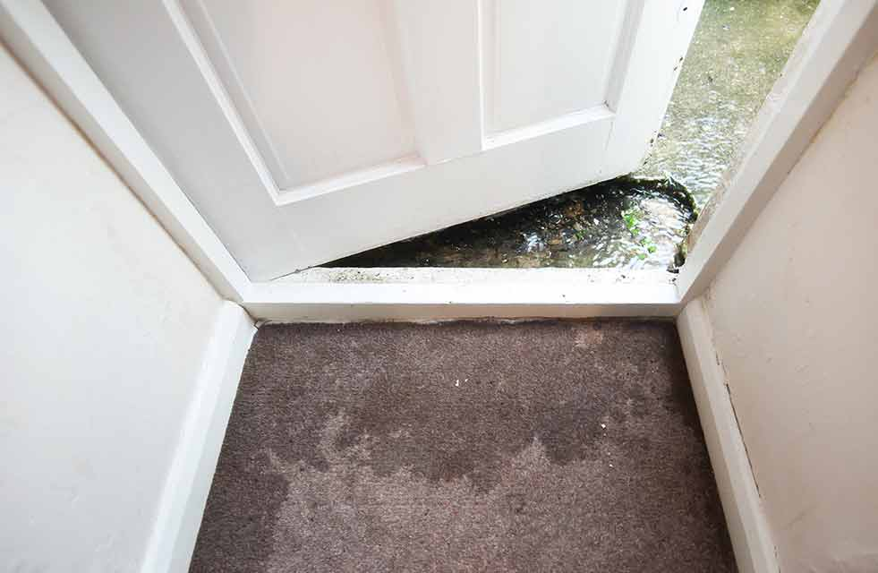 Water flooding into garage and home with door cracked open