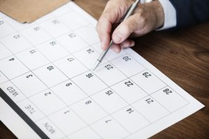 Man pointing at paper calendar