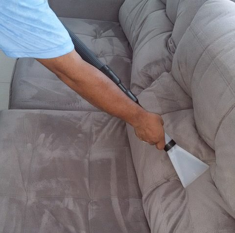 Man Cleaning Couch with Vacuum/Steamer
